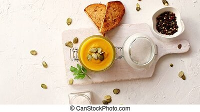 Pumpkin soup in glass jar on cutting board - From above view...