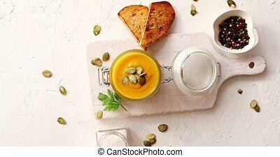 Pumpkin soup in glass jar on cutting board