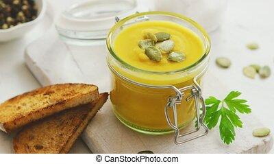 Pumpkin soup in glass jar with bread - Yellow pumpkin soup ...