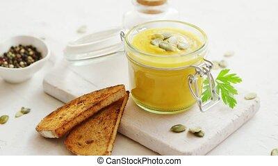 Pumpkin soup in glass jar with bread