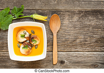 Pumpkin soup on a wooden table background