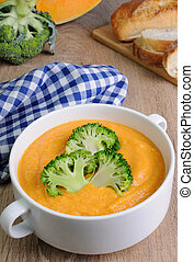 Pumpkin soup puree with cream in a dish with broccoli