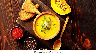 Pumpkin soup with bread on chopping board - From above view...