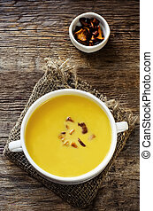 pumpkin soup with chanterelles on a dark wood background. ...