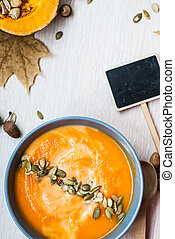 Pumpkin soup with cream and pumpkin seeds on a white wooden table. top view