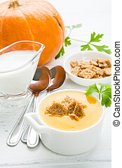 Pumpkin soup with crutons on white wooden table, vertical...