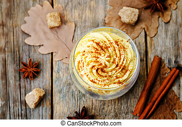 pumpkin spice cheesecake mousse on a dark wood background. ...