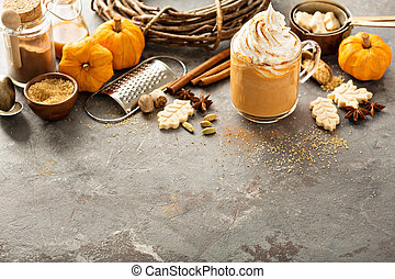 Pumpkin spice latte in a glass mug with cinnamon, nutmeg and...