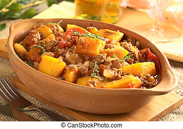 Pumpkin, tomato, mincemeat dish with fresh thyme (Selective Focus, Focus on the pumpkin piece on the top of the meal)