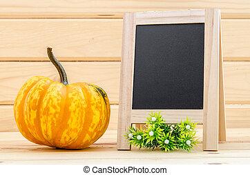 pumpkin with a blank chalk board.