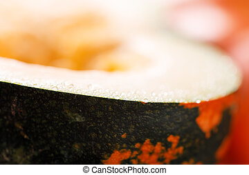 Pumpkin with dark green and orange spots. A slice of pumpkin with fresh pulp.