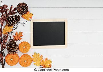 Pumpkins and Chalkboard over Wooden Background
