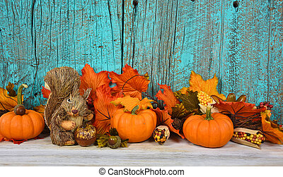 pumpkins and fall leaves on wood