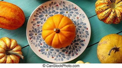 Pumpkins laid on plate and near - From above view of orange...