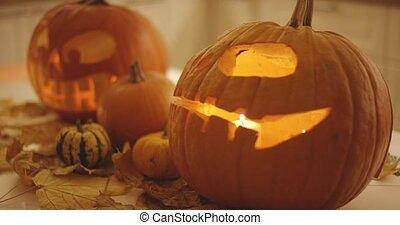Pumpkins near jack-o-lanterns - Three small pumpkins lying...