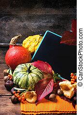 Pumpkins, nuts and empty chalkboard