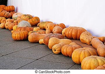 Pumpkins on asphalt as autumn decoration at market place
