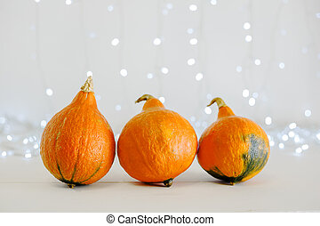 Pumpkins on white background with lights. Happy Halloween party invitation, celebration. Halloween decorations concept. Copy space. Autumn cozy home.