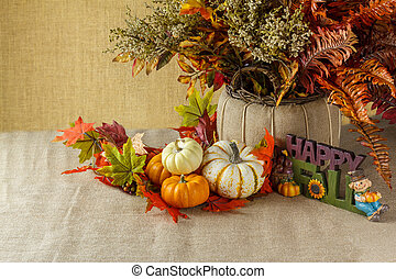 Pumpkins with fall leaves on sackcloth