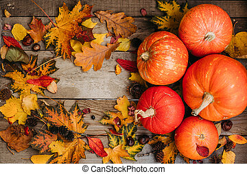 Pumpkins with fall leaves over wooden background. Orange halloween pumpkins in autumm composition.