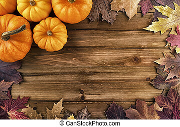 Pumpkins With Fall Leaves Over Wooden Background Top View