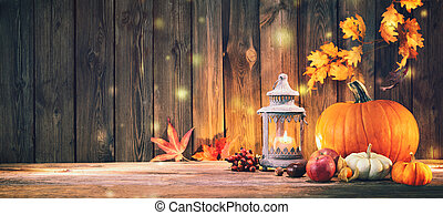 Pumpkins with fruits and falling leaves on rustic wooden table