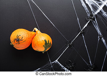 Pumpkins with spiders and spider web on black background. Halloween holiday decorations. Flat lay, top view, copy space.