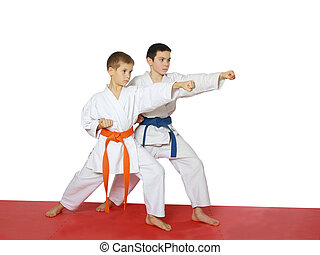 Strong punch hand in the performance of athletes with a blue belt and orange belt