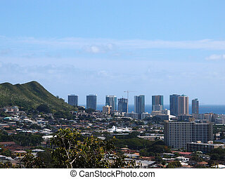 Punchbowl Crater, Nuuanu, and Honolulu Cityscape looking to the ocean from high up in the hills with cranes and modern skycrapers mixed with houses, and other small buildings.