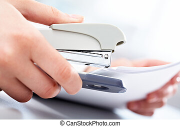 Puncher - Close-up of female hand stapling the documents