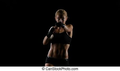 Punches and kicks by delightful athlete girl boxer. Slow motion