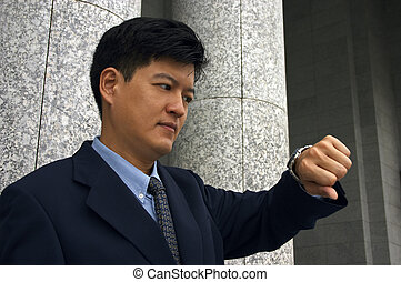 Punctuality - Asian man in a business suit looking at the...