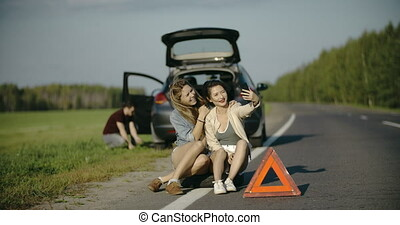 Puncture wheel man changing tire help two female friends...