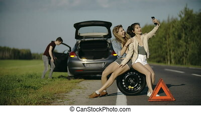 Puncture wheel man changing tire help two female friendstake...