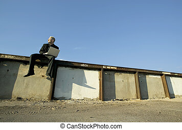 Punk Businessman on a Wall with Laptop Computer