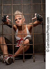 Punk girl behind bars showing rude gesture.