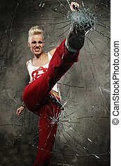 Punk girl breaking glass with her boot