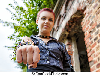 punk girl showing leather bracelet with metal spikes