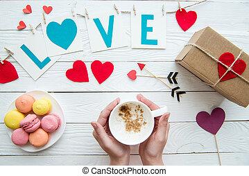 punta la vista, de, manos humanas, sostener la taza, de, capuchino, con, macarrón, galletas, romántico, decoración, en, de madera, fondo., día de valentines, composición