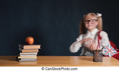 Happy schoolgirl with shiny red backpack came for lesson into the classroom, standing joyfully near the desk with arranged books and red apple on the top, concept of the start of study