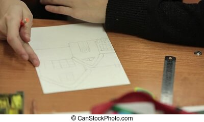 Pupil drawing house on paper in class