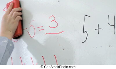 Pupil erases equation mathematics from board - Pupil erases...
