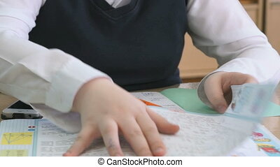 Pupil flips pages of tutorial during the lesson