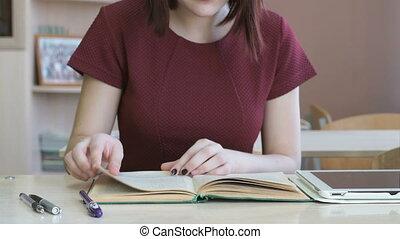 Pupil girl sitting at desk reading school tutorial. Close-up