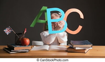 Pupil Learns ABC - Primary pupil learning abc, wearing big...