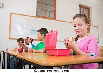 Pupil opening lunchbox at desk - Cute pupil opening lunchbox...
