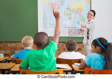 Pupil raising hand in classroom at the elementary school