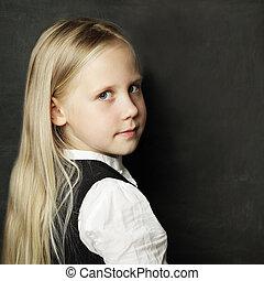 Pupil with school blackboard, face closeup
