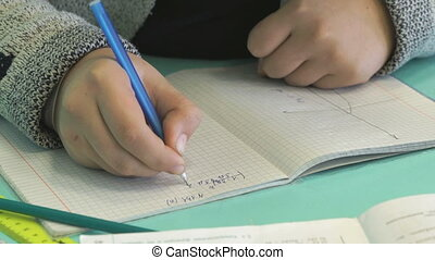 Pupil writes text in a notebook indoors