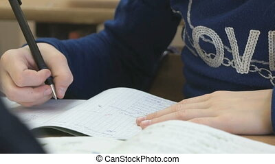 Pupil writes the text in a notebook indoors